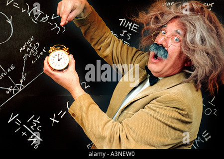Clock being held by mad professor looking like Einstein with E=MC2 on blackboard with equations about time, time - Stock Photo