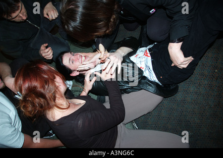 young man is tickled to the floor in nightclub dsc 5104 - Stock Photo