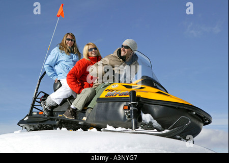 young people on snowmobile - Stock Photo