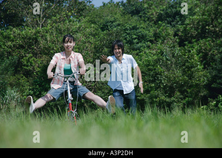 Young woman riding on bicycle and a man following - Stock Photo