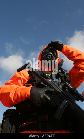 A British armed police officer dressed in an anti nuclear chemical warfare suit - Stock Photo