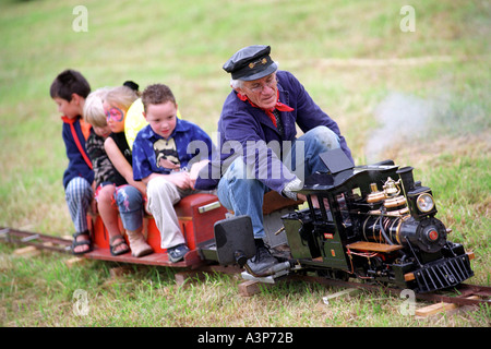 A model steam train taking children for a ride at a village fete in Dorset Britain UK - Stock Photo