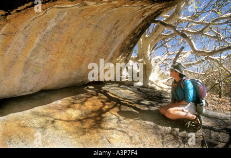 Female tourist looking at cave art under an overhang near Inanke Cave Zimbabwe - Stock Photo