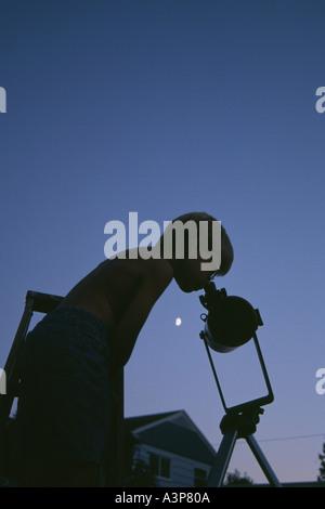 boy looking thru reflecting telescope - Stock Photo