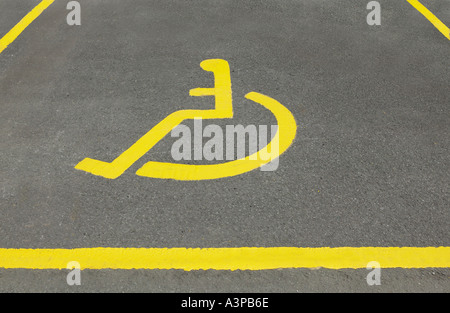 PAINTED YELLOW ICON OF WHEELCHAIR IN DISABLED PARKING BAY - Stock Photo