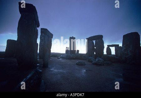 The massive Sarsen stones of Stonehenge circle silhouetted against breaking storm clouds Wiltshire - Stock Photo