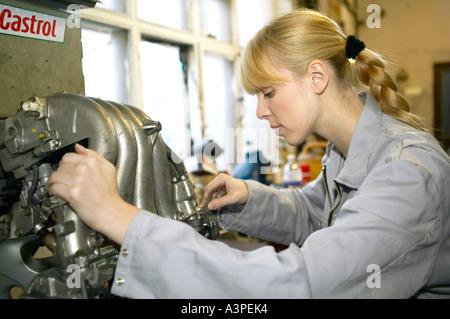 female motor mechanic working on the car motor - Stock Photo