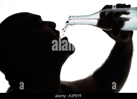Young man pouring bottled water in to mouth - Stock Photo