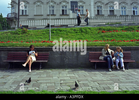 People sitting on benches in Przemysl, Poland - Stock Photo
