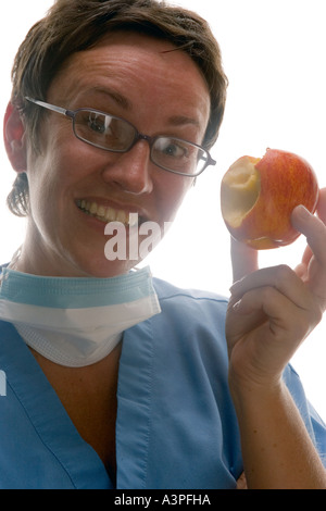 Female Dietitians, Nutritionists,  doctor eating apple - Stock Photo