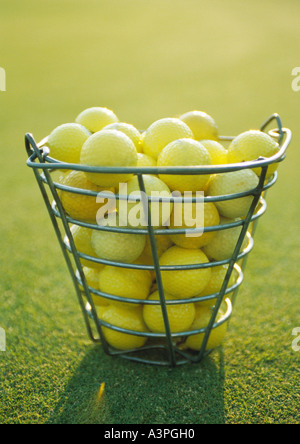 Basket of yellow golf balls - Stock Photo