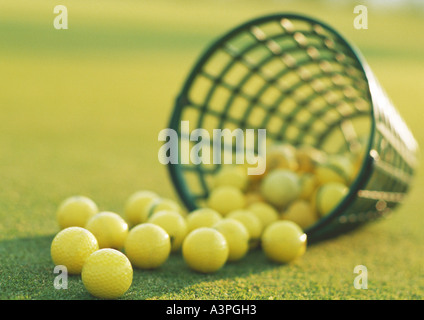 Spilled basket of yellow golf balls, close-up - Stock Photo