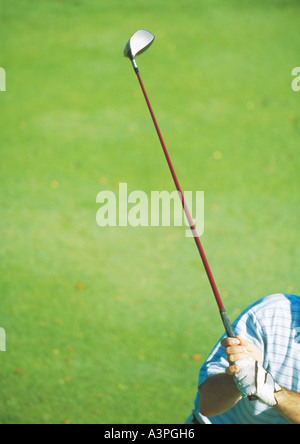 Golfer swinging club, partial view - Stock Photo