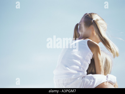 Little girl riding on mother's shoulders - Stock Photo