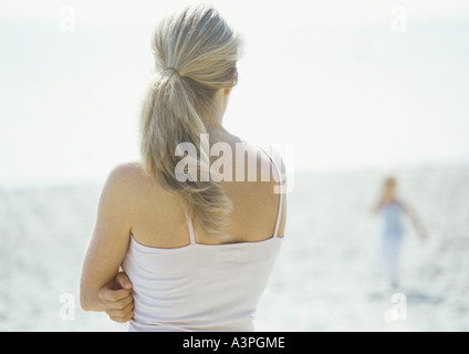 Woman looking toward child on beach, rear view - Stock Photo