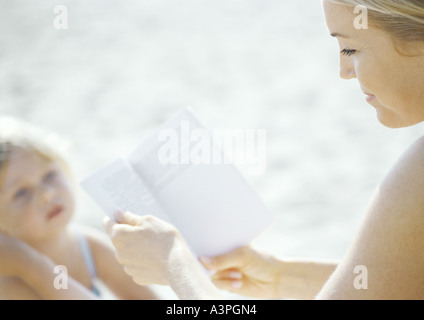 Woman reading book, child looking up at woman - Stock Photo