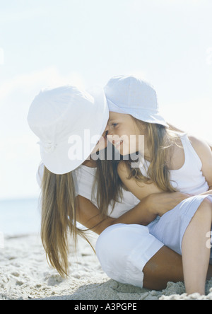 Girl sitting on mother's lap on beach - Stock Photo