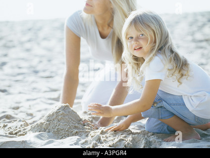 Girl and mother playing in sand - Stock Photo