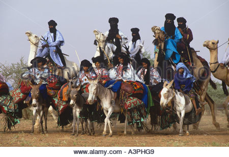 Men riding camels women on donkeys with their possessions arriving at wedding celebrations central Niger - Stock Photo