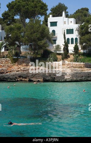 Tourists swimming in cobalt blue water, Majorca, Spain - Stock Photo