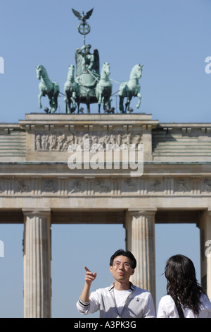 Asian tourists in front of the Brandenburg Gate in Berlin, Germany - Stock Photo