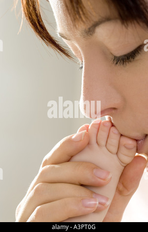 mother kissing baby's foot - Stock Photo