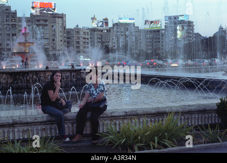 Two women sitting at a fountain in a park at the Unity Square (Piata Unirii), Bucharest, Romania - Stock Photo