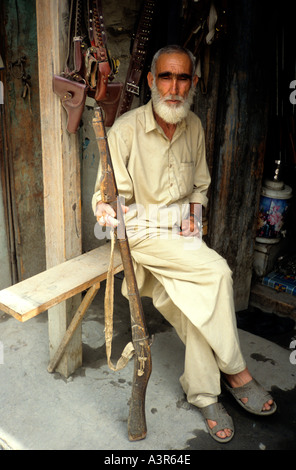 Gunsmith holding ancient gun in the main street bazaar in Chitral on the Noth Western frontier of Pakistan with - Stock Photo