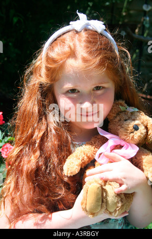 6 year old girl with long red hair holding teddy bear - Stock Photo