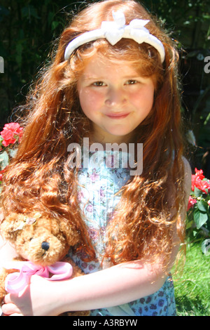 little girl with red hair and a teddy bear - Stock Photo