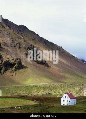 Solitary house in Arnarstapi village below Mount Stapafell on the Snaefellsnes peninsular in Arnarstapi Iceland - Stock Photo