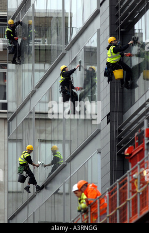 ABSEILING WINDOW CLEANERS WORK ON  A HIGH RISE BUILDING  RE HEALTH AND SAFETY DANGEROUS JOBS OCCUPATIONS WORKERS - Stock Photo