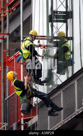 ABSEILING WINDOW CLEANERS WORK ON A BIRMINGHAM CITY BUILDING RE HEALTH AND SAFETY DANGEROUS JOBS CAREERS WORKERS - Stock Photo