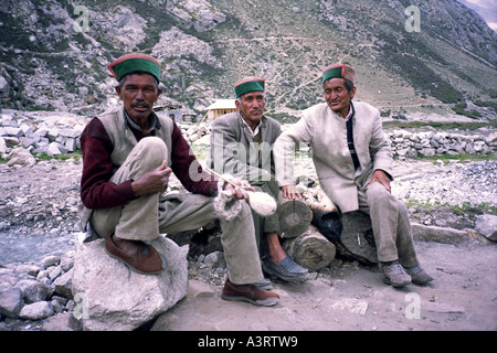 Three local men wearing traditional Kinnauri hats (Thepang) sit in Chitkul village, Sangla Valley, Himachal Pradesh - Stock Photo