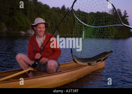 A fisherman and northern pike esox lucius caught from a canoe in Craig Lake State Park near Michigamme Michigan - Stock Photo