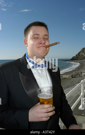 Male student in Dinner jacket smoking cigar and drinking pint of beer Aberystwyth University may ball, on the promenade - Stock Photo