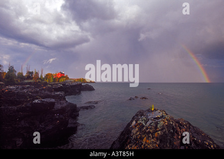 A rainbow arches over the Marquette Lighthouse in Marquette Michigan on Lake Superior - Stock Photo