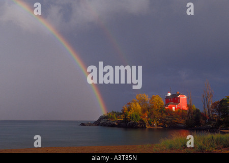 A rainbow arches over Lake Superor near the Marquette Lighthouse in Marquette Michigan - Stock Photo