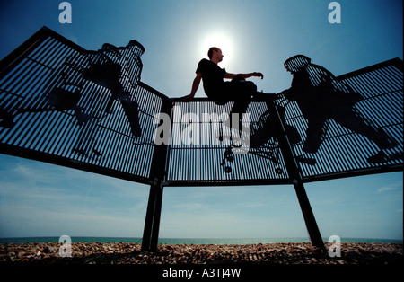 Silhouette of young man perched on top of modern fencing on pebble beach with sea in background. - Stock Photo