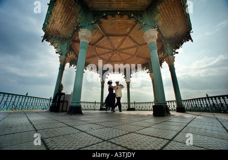 Ballroom Dancers on the disused Victorian bandstand on Brighton seafront during the annual arts festival - Stock Photo
