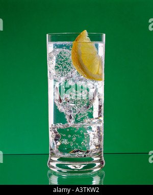 Gin and tonic with ice and lemon in long glass - Stock Photo