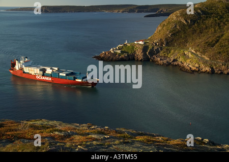 Canada Newfoundland St John s container ship entering harbour narrows Fort Amherst Lighthouse - Stock Photo