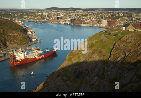 Canada Newfoundland St John s container ship entering harbour from narrows downtown skyline view from Signal Hill - Stock Photo