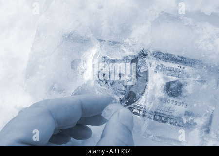 Hand finding frozen money in ice - Stock Photo