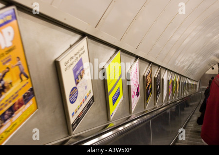 View down an escalator in the London underground with advertising posters - Stock Photo