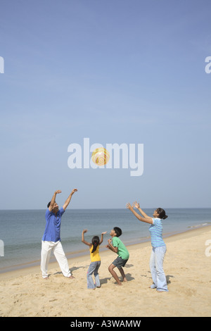 Family of four enjoying on picnic playing with rubber ball on the beach - Stock Photo