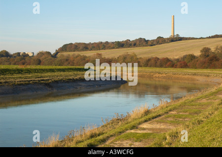 The river Adur winds its way to Shoreham. The chimney from the now derelict cement works is visible in the background. - Stock Photo
