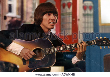 BEATLES - George Harrison with his Gibson acoustic guitar in the 1965 United Artists film HELP - Stock Photo
