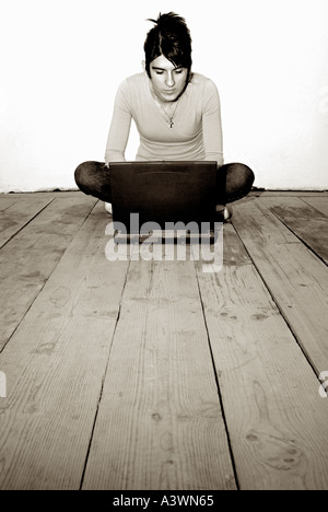 Woman Sat on Bare Wooden Floorboards Using a Laptop - Stock Photo