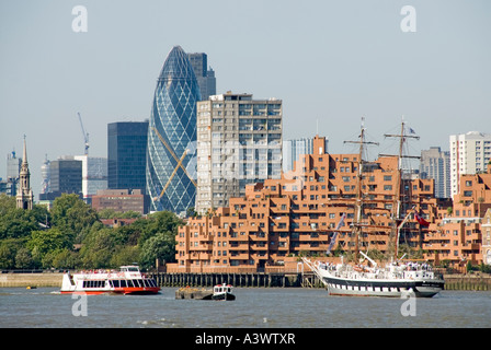 River Thames waterside apartment development with City skyline beyond including Gherkin Tower and tall ship passing - Stock Photo
